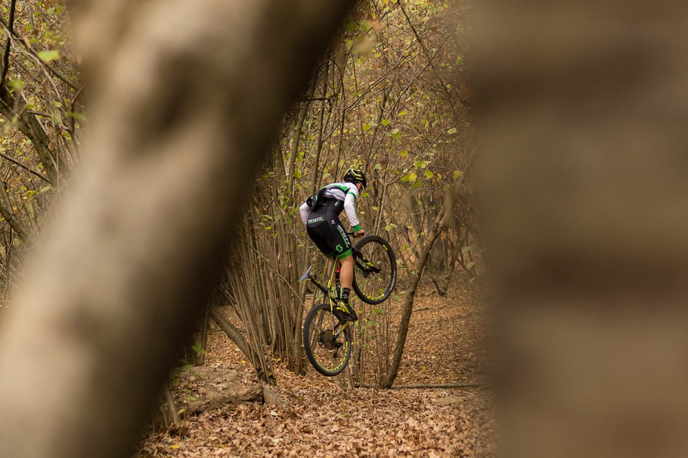 man riding on black mountain bike