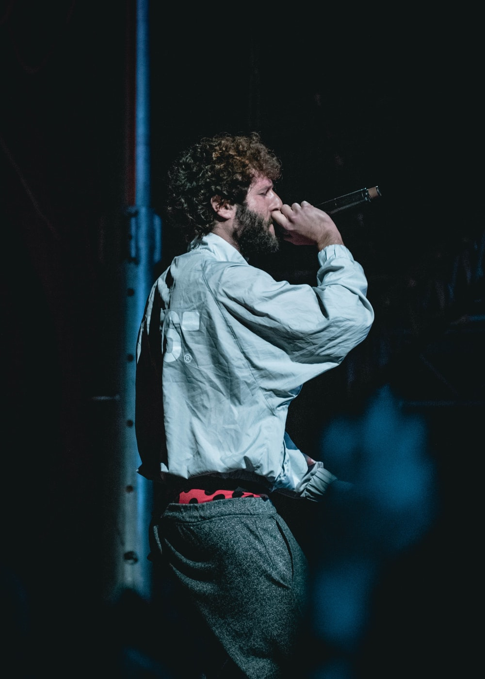 man holding cordless microphone on stage