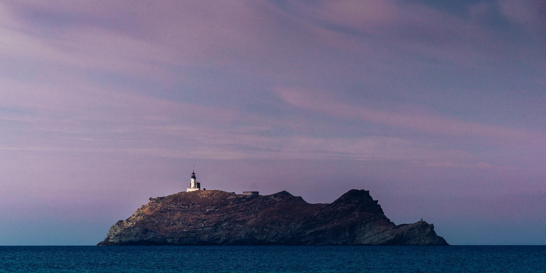 white and black lighthouse on island