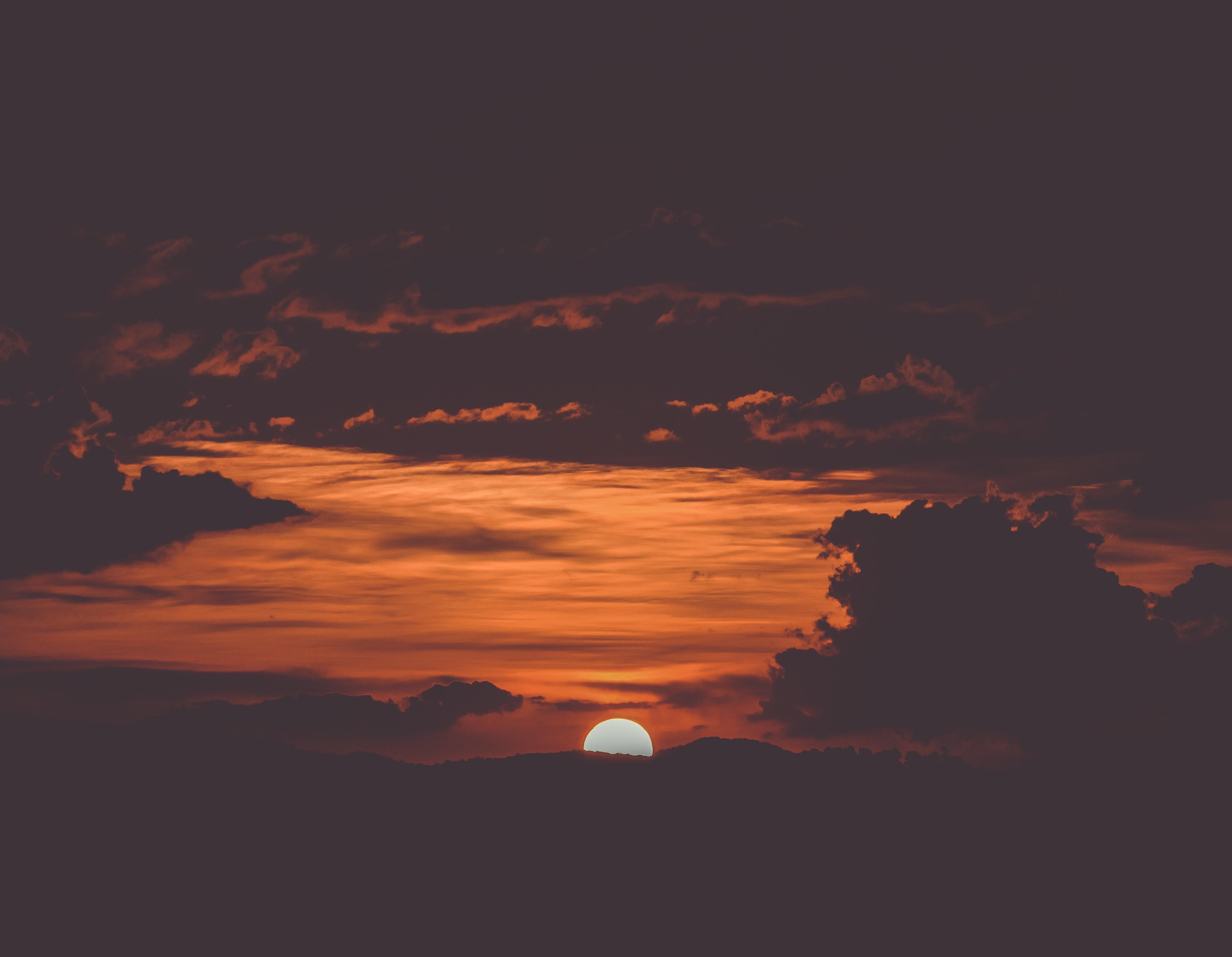 photo of sun setting beyond the horizon