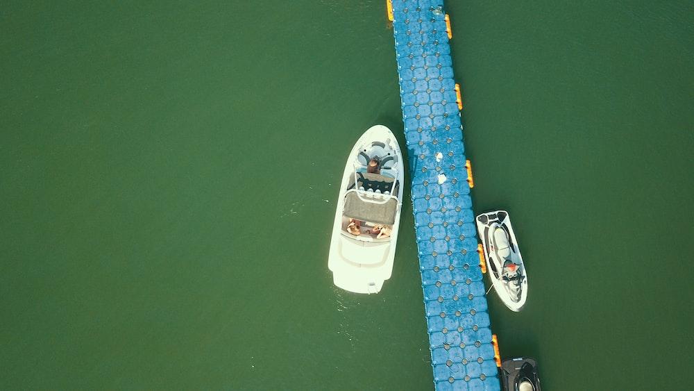 two white speedboats on body of water beside blue dock