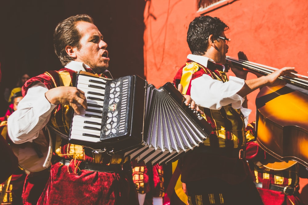 two men playing cello and accordion beside red building photo