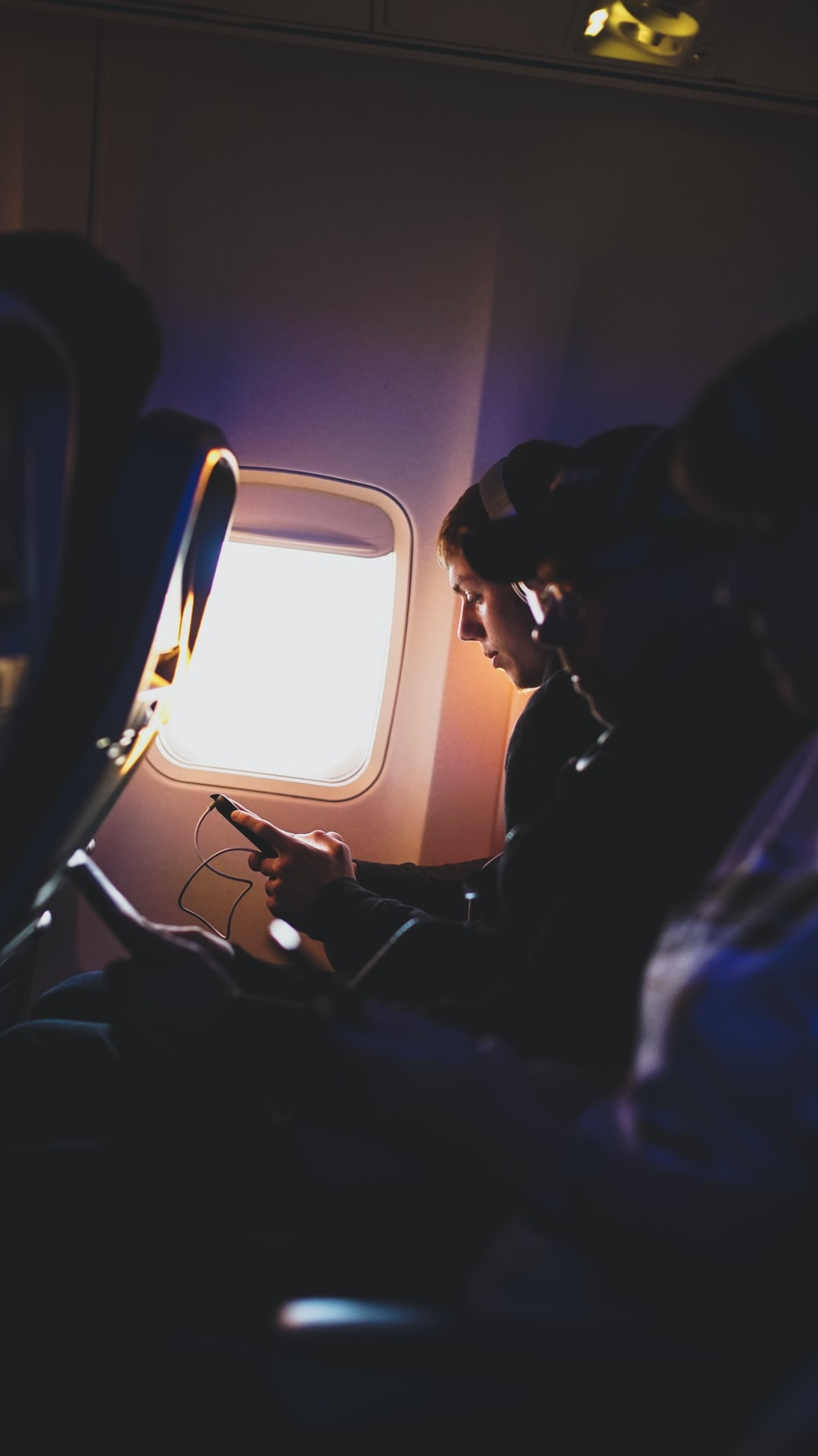 photo of three people listening to music inside airplane