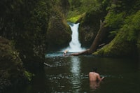 person on body of water near waterfalls during daytime