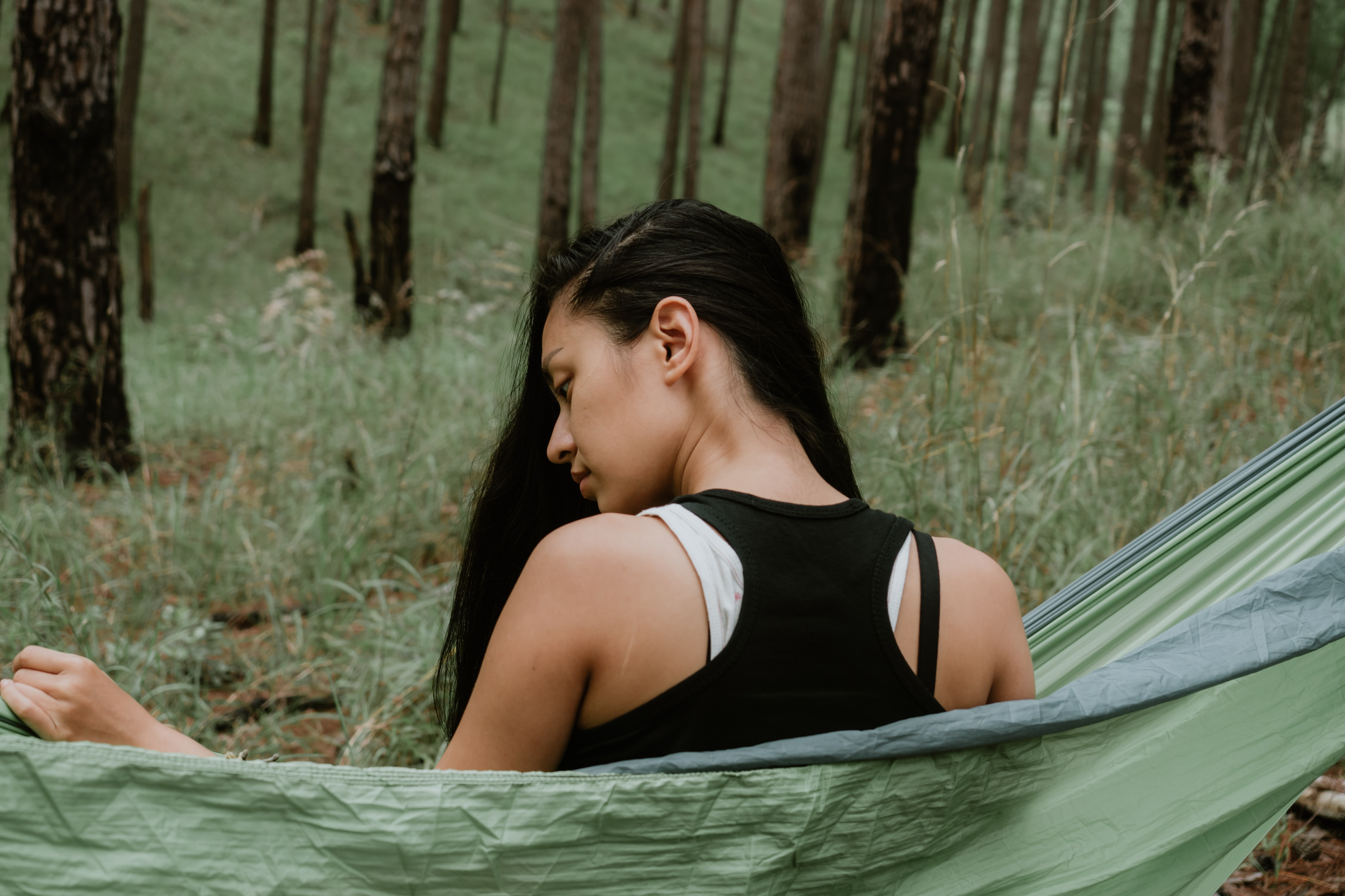 woman in black top sitting on green hammock