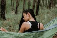 woman in black top sitting on green hammock