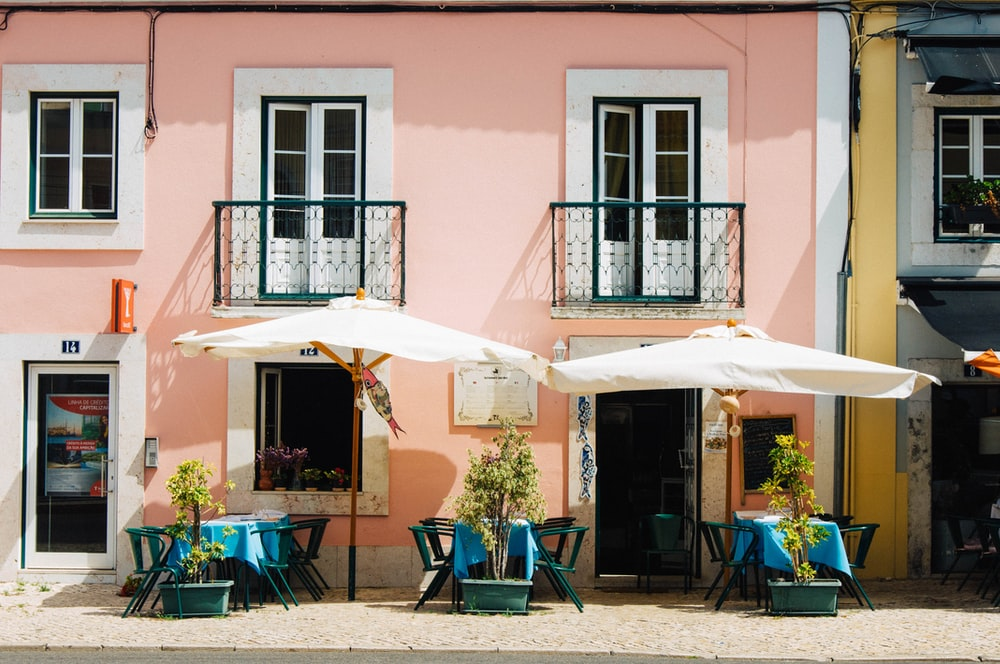 two white patio umbrellas near pink and white painted concrete building