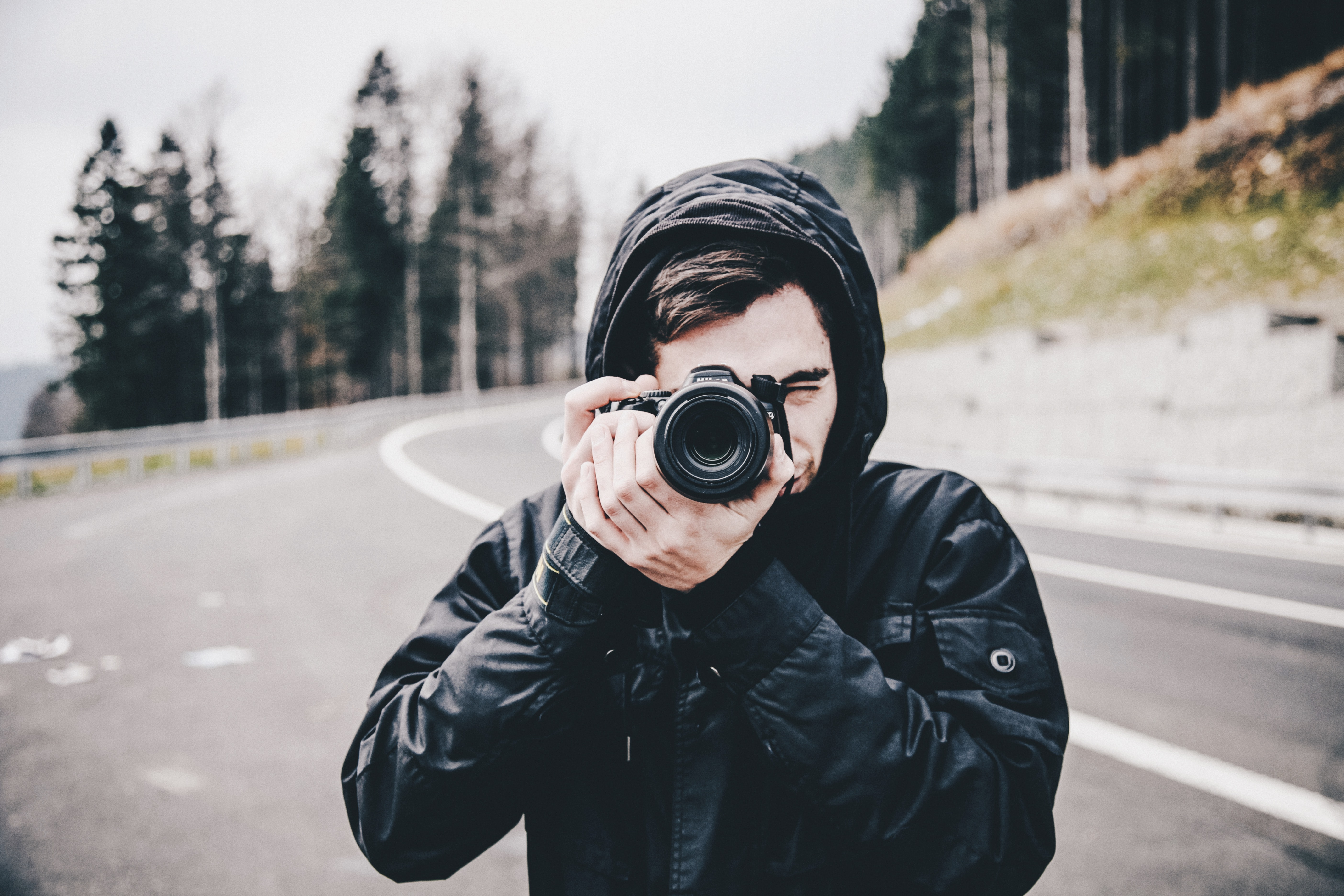 man in black jacket taking picture with DSLR camera on road