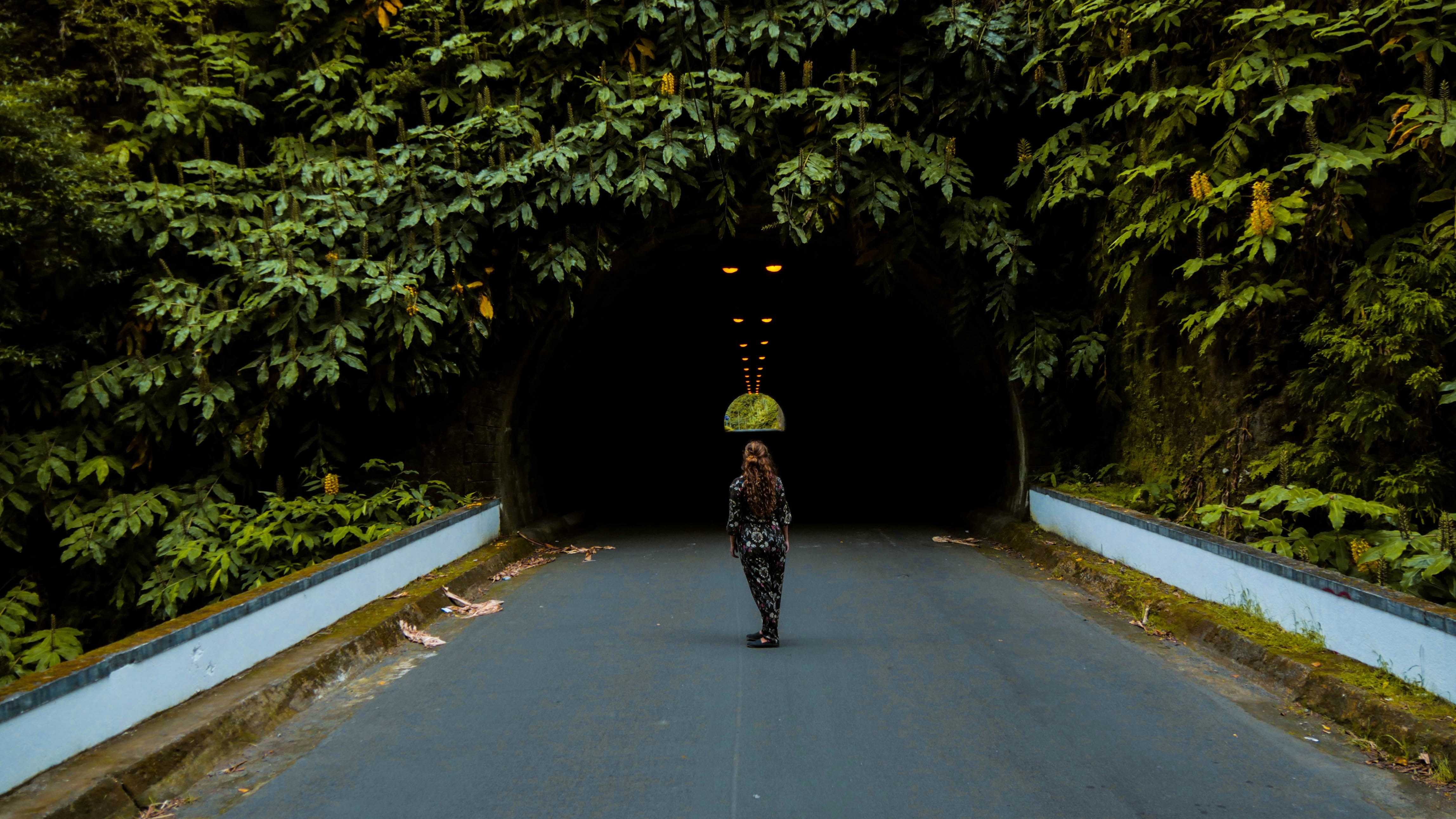woman standing in the middle of the road staring at tunnel