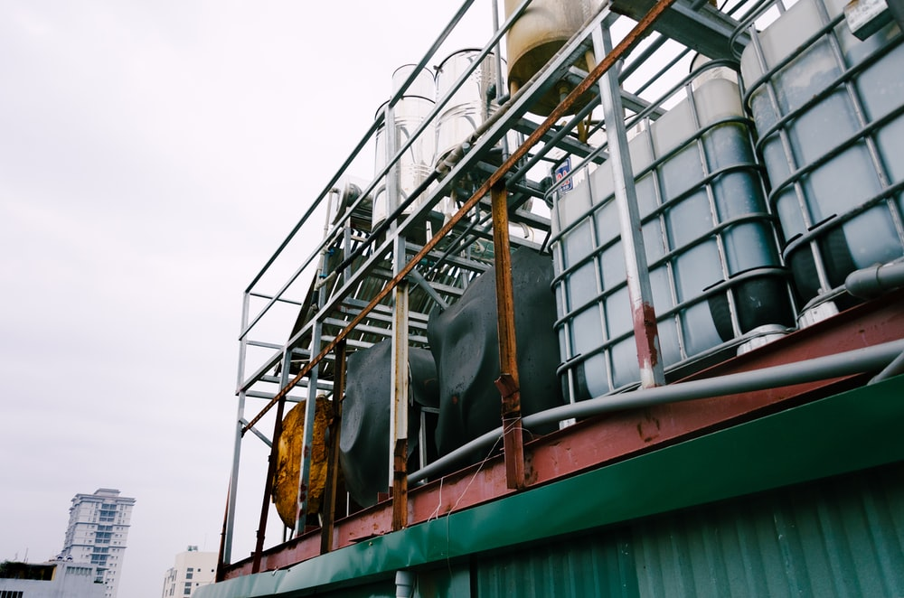 white IBC tanks on green building