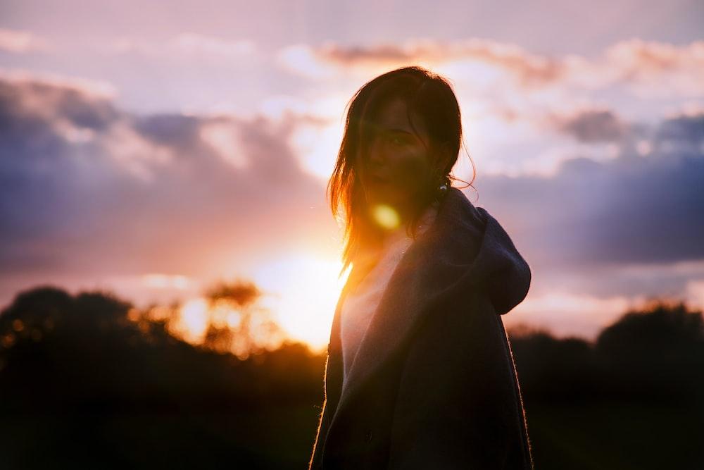 woman wearing gray hoodie during sunset