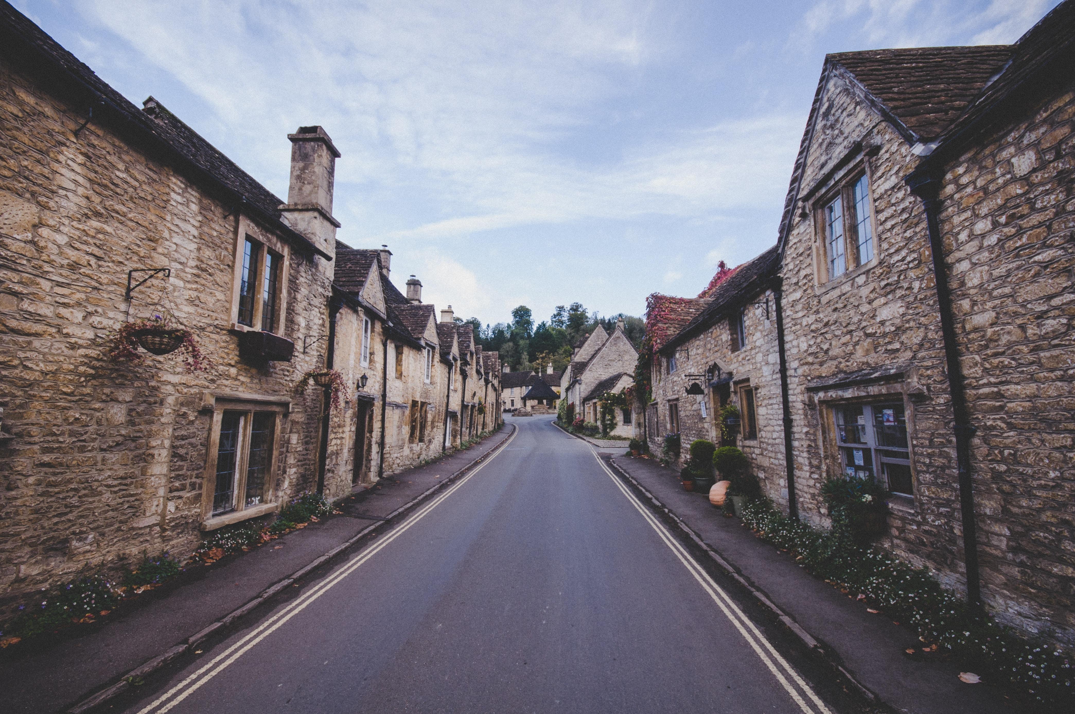 concrete road between brick wall buildings