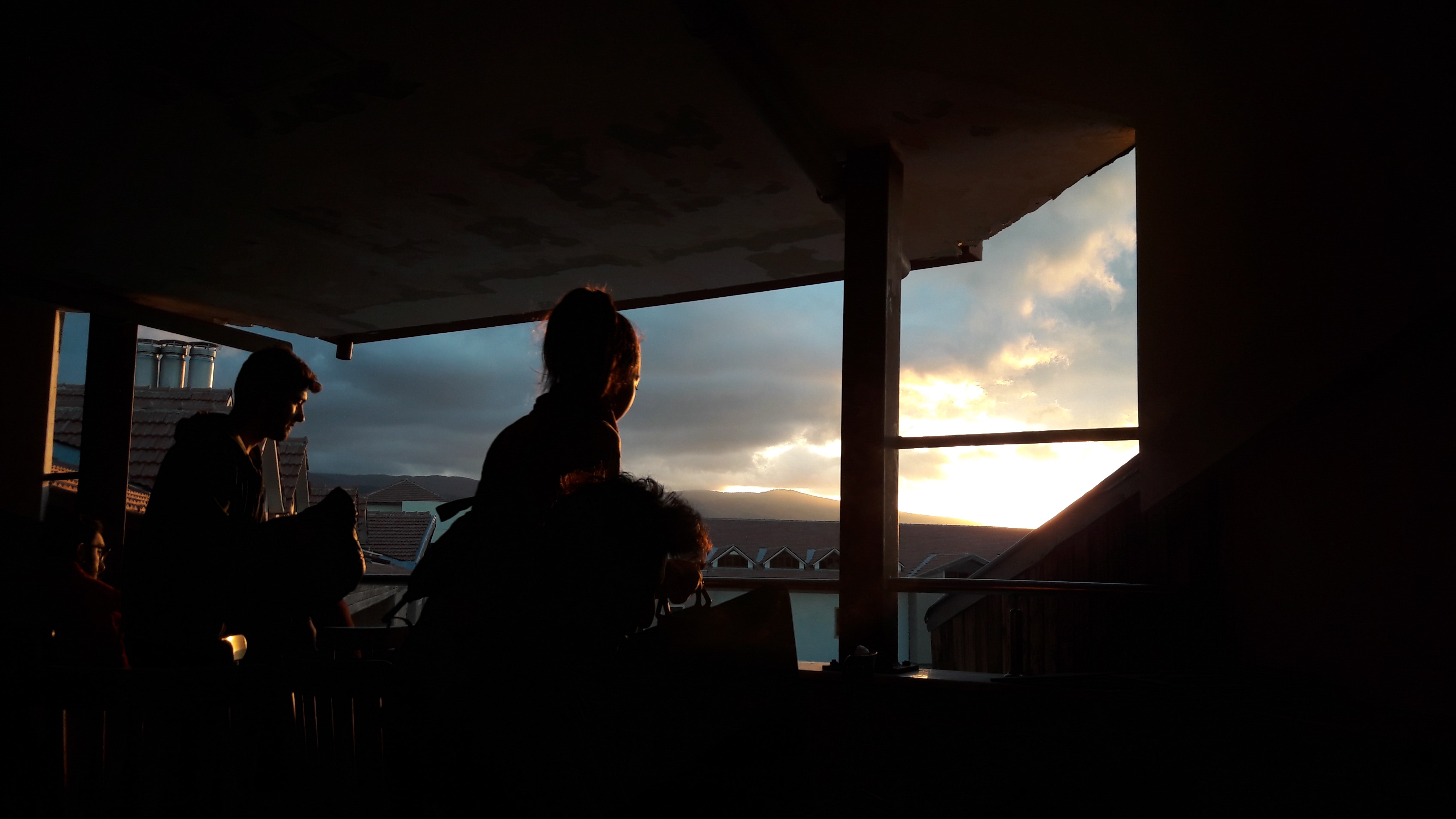silhouette of two persons standing near the window
