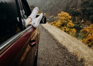 person's feet wearing white Converse sneakers on car door