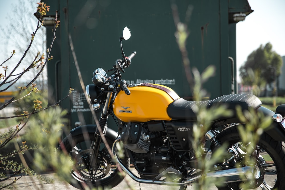 yellow and black standard motorcycle near green wall
