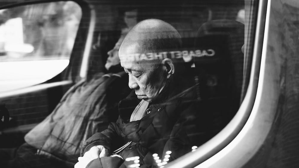 grayscale photo of man inside vehicle sleeping