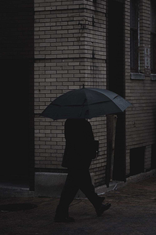 person holding umbrella walking on concrete pavement near building
