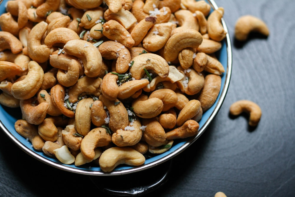 cashew nut lot on blue ceramic bowl