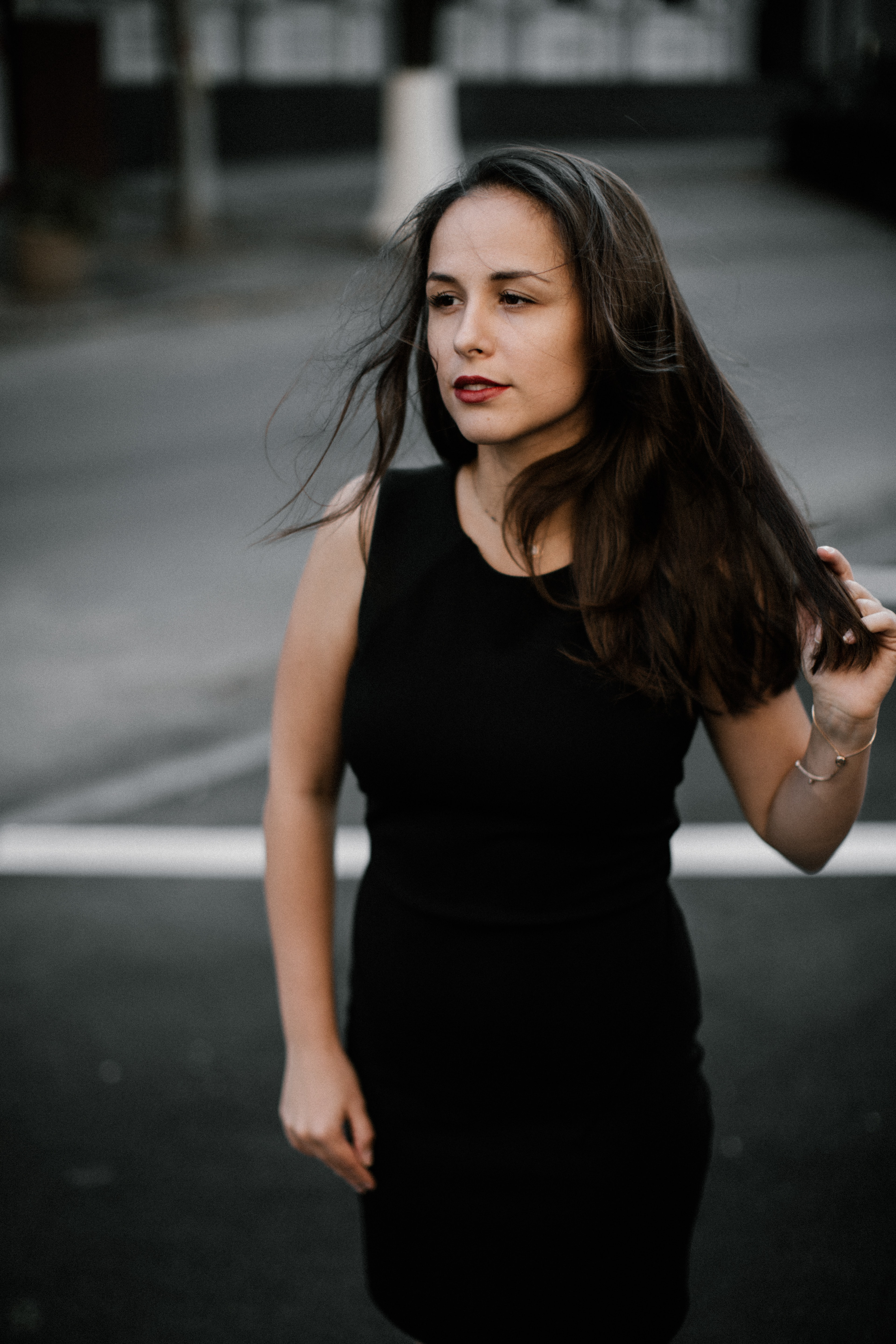 focus photo of woman in black sleeveless dress walks on road