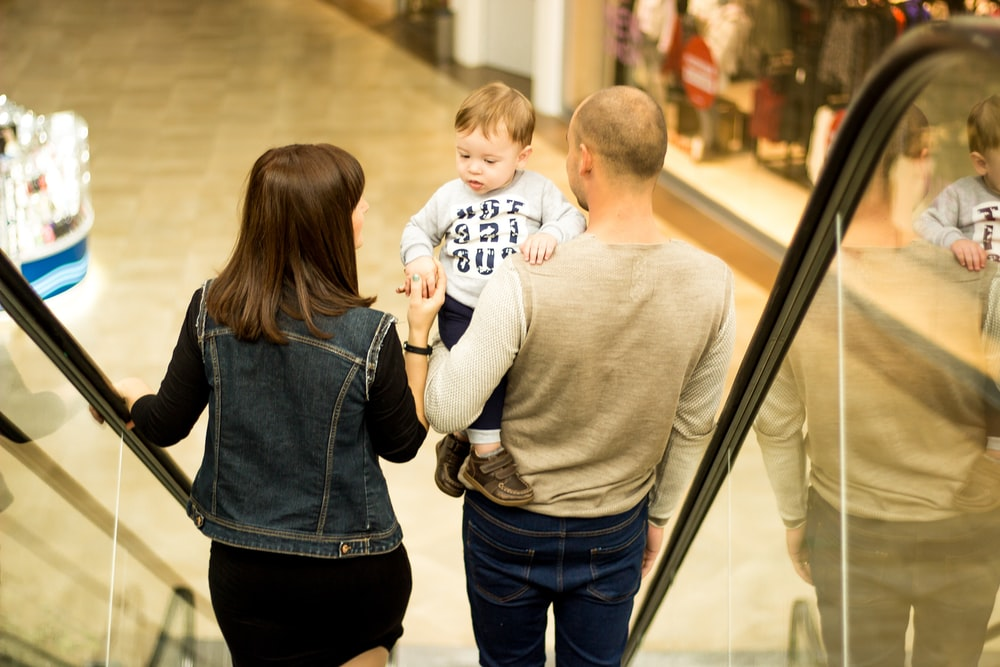 man, woman, and child standing on escalator