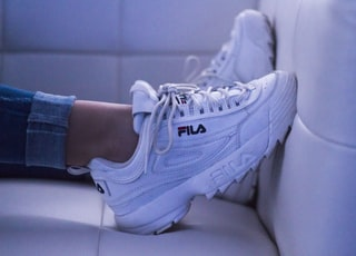 woman wearing white Fila shoes
