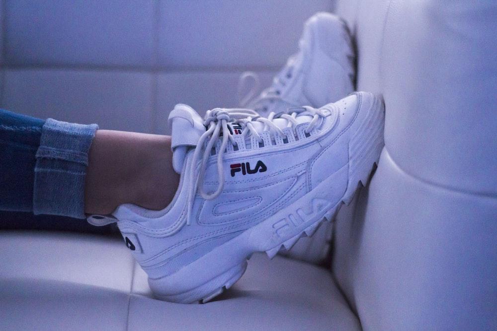 woman wearing white Fila shoes