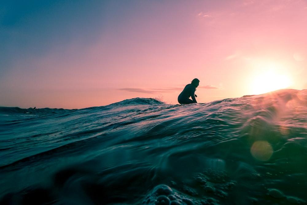 man surfing on ocean water during golden hour