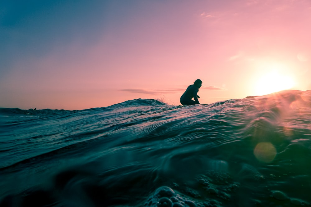 man surfing on ocean water during golden hour