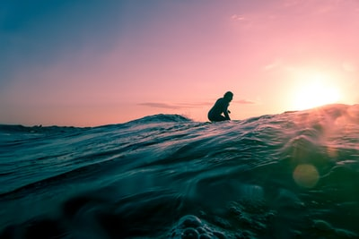 man surfing on ocean water during golden hour surfing teams background