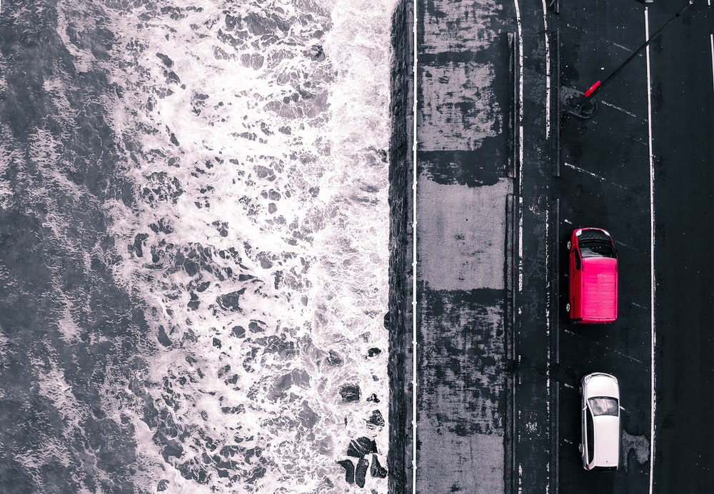 aerial photography of two vehicles near sea