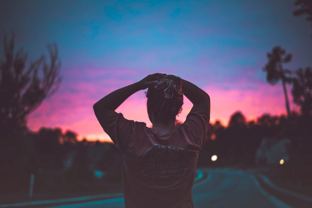 silhouette photography of woman holding her head