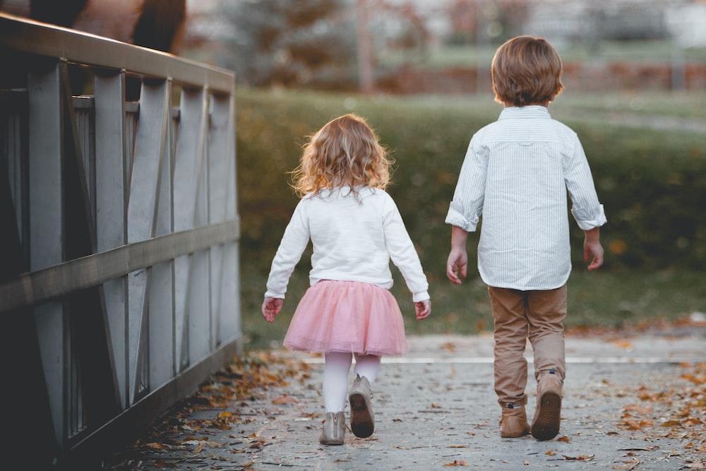 boy beside girl walking near railing