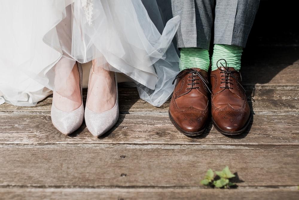two people standing on brown wooden floor