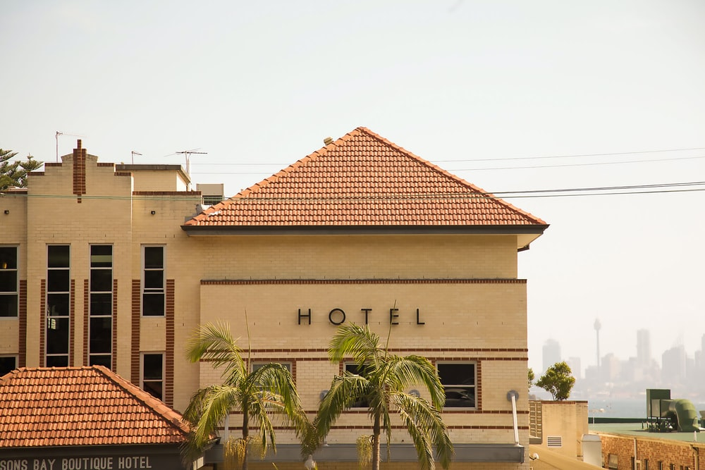 photo of brown concrete Hotel with two coconut trees