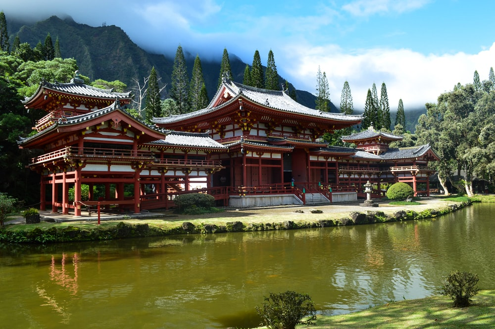red wooden framed temple near body of water during daytime