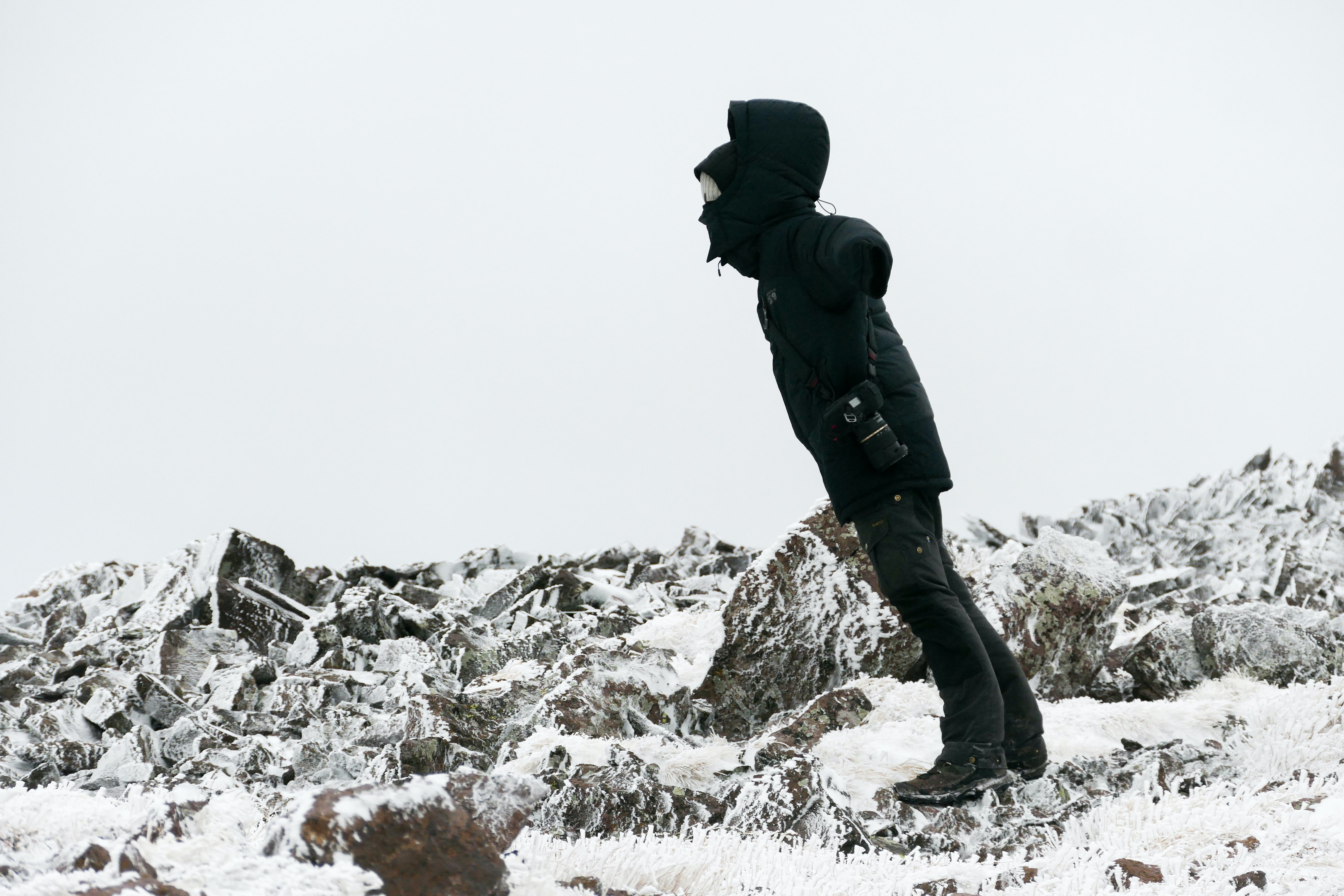 man standing on stone covered with snow