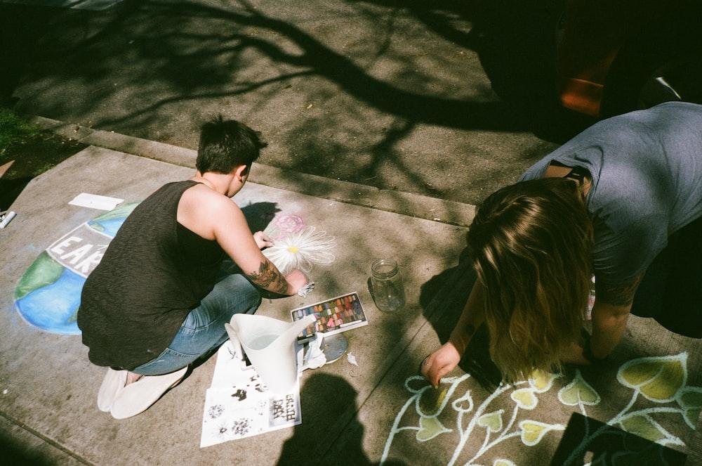 man and woman painting at gray platform