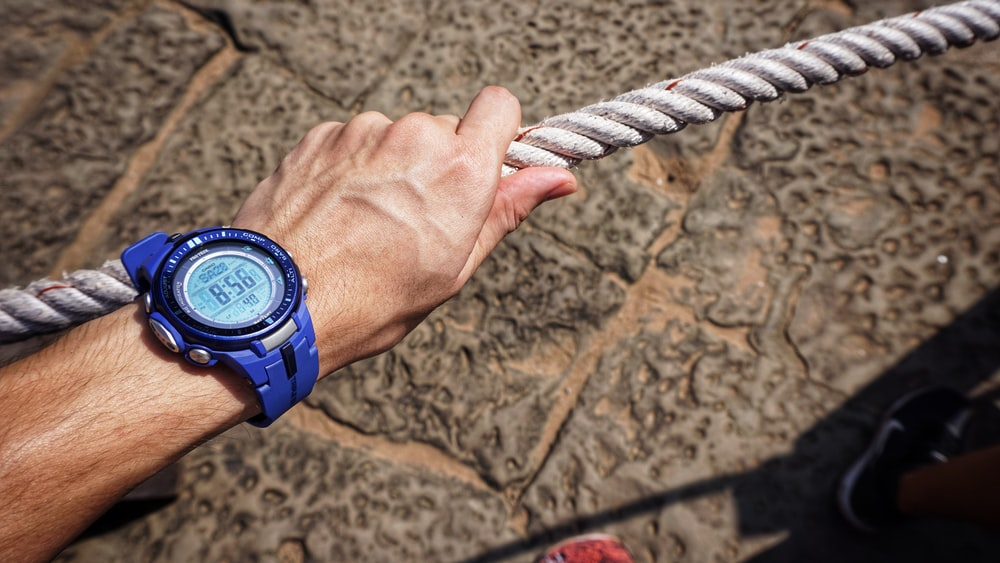 person wearing blue digital watch with strap