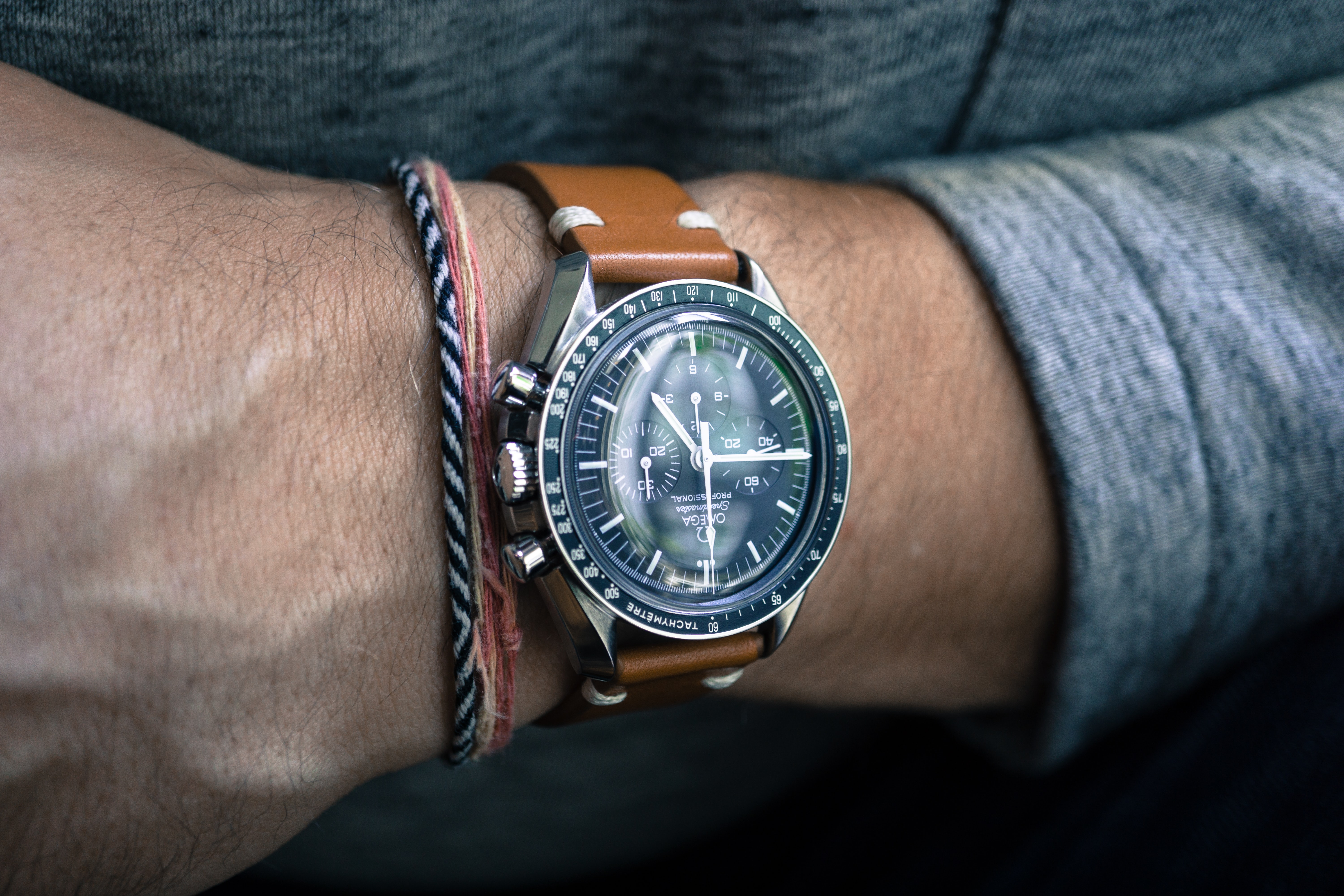 person wearing round silver-colored bezel chronograph watch with brown leather strap