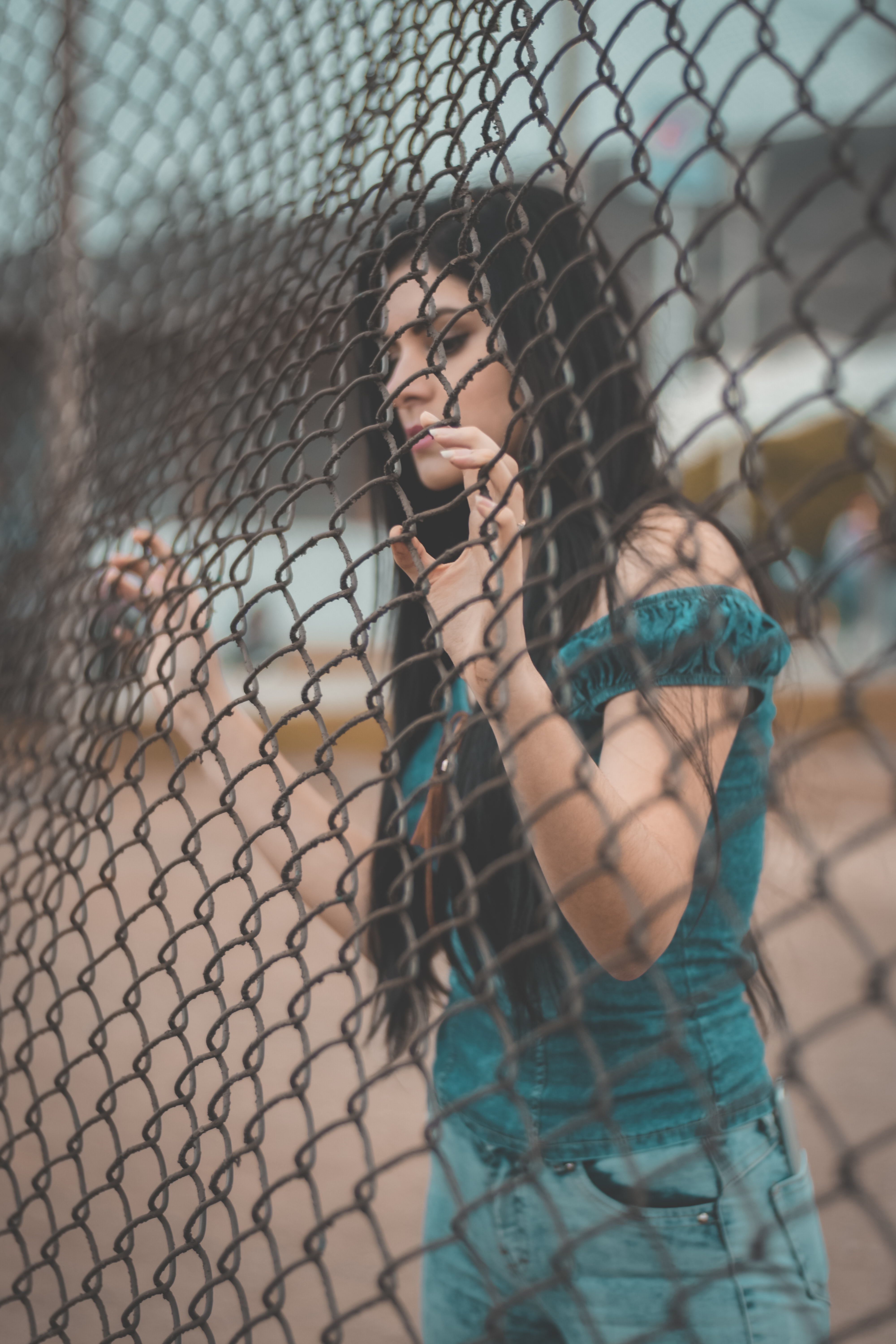 photography of woman touching gray metal fence
