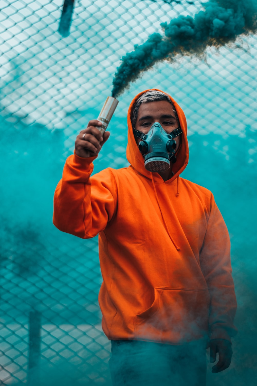 man wearing orange pullover hoodie holding smoke flare