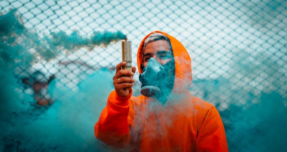 man holding blue smoke flare during daytime
