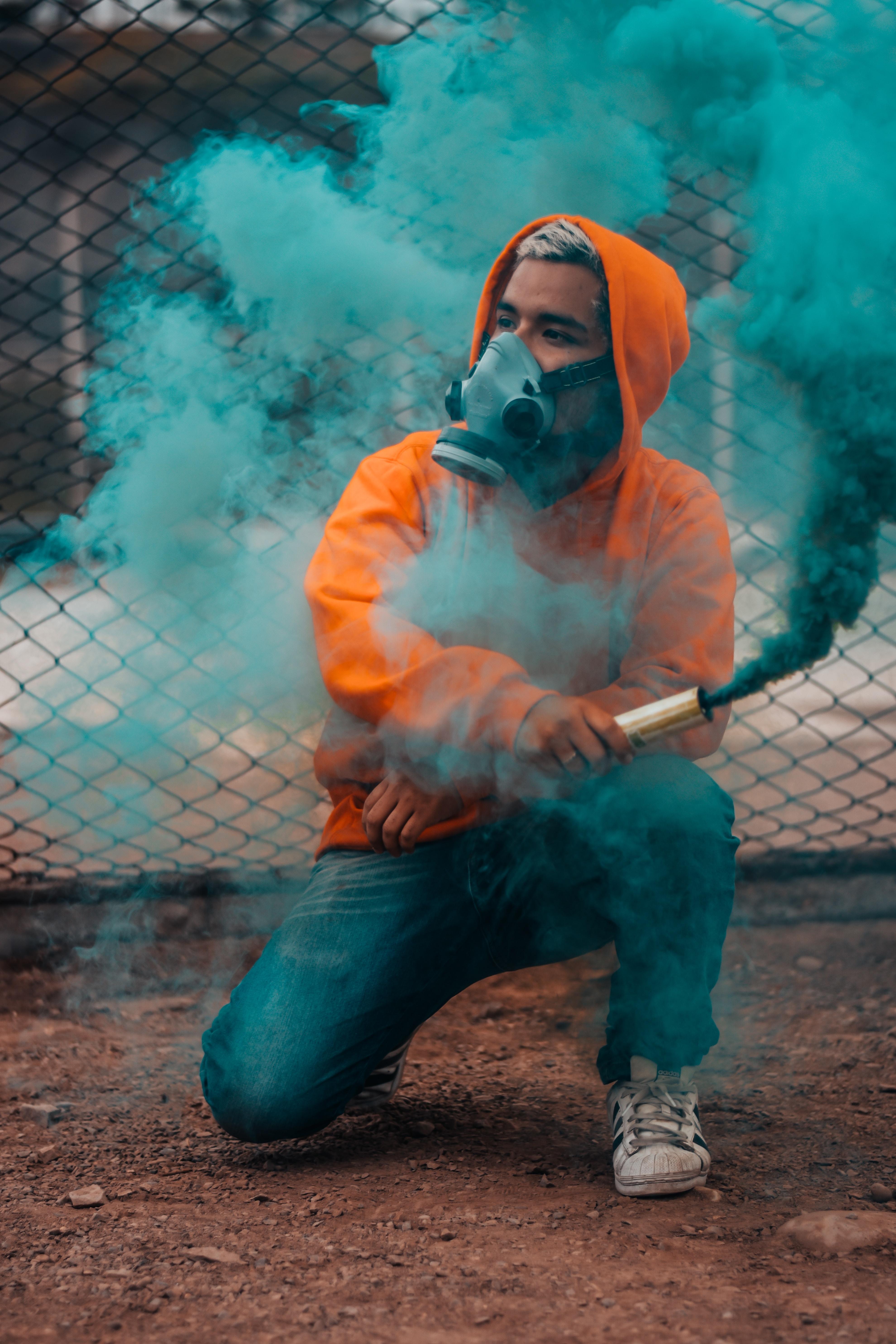 man holding tube with green smoke during daytime photo