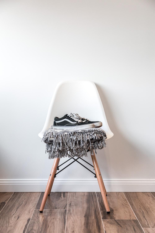 pair of black low-top Vans sneakers on white chair