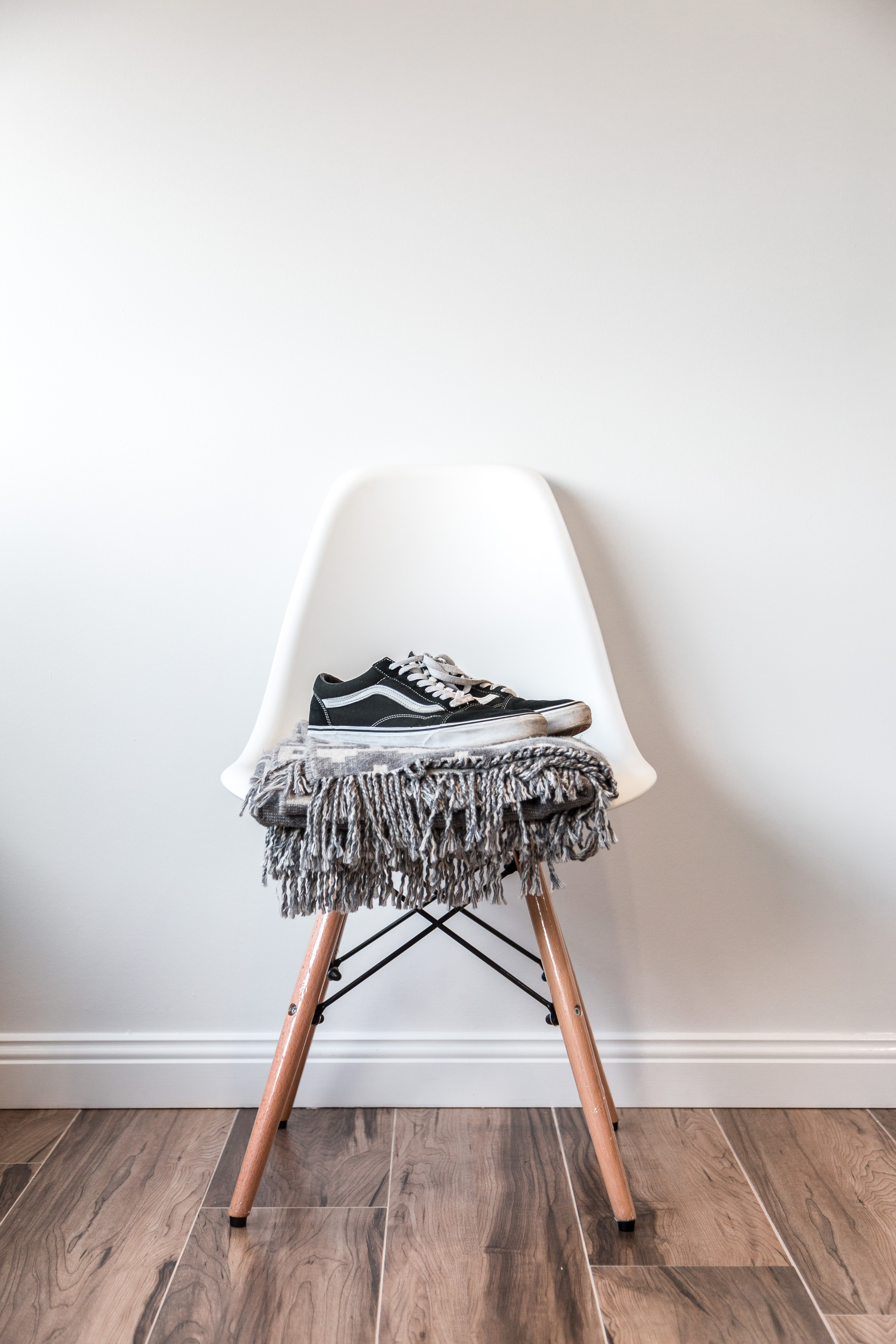 pair of black low-top Vans sneakers on white chair
