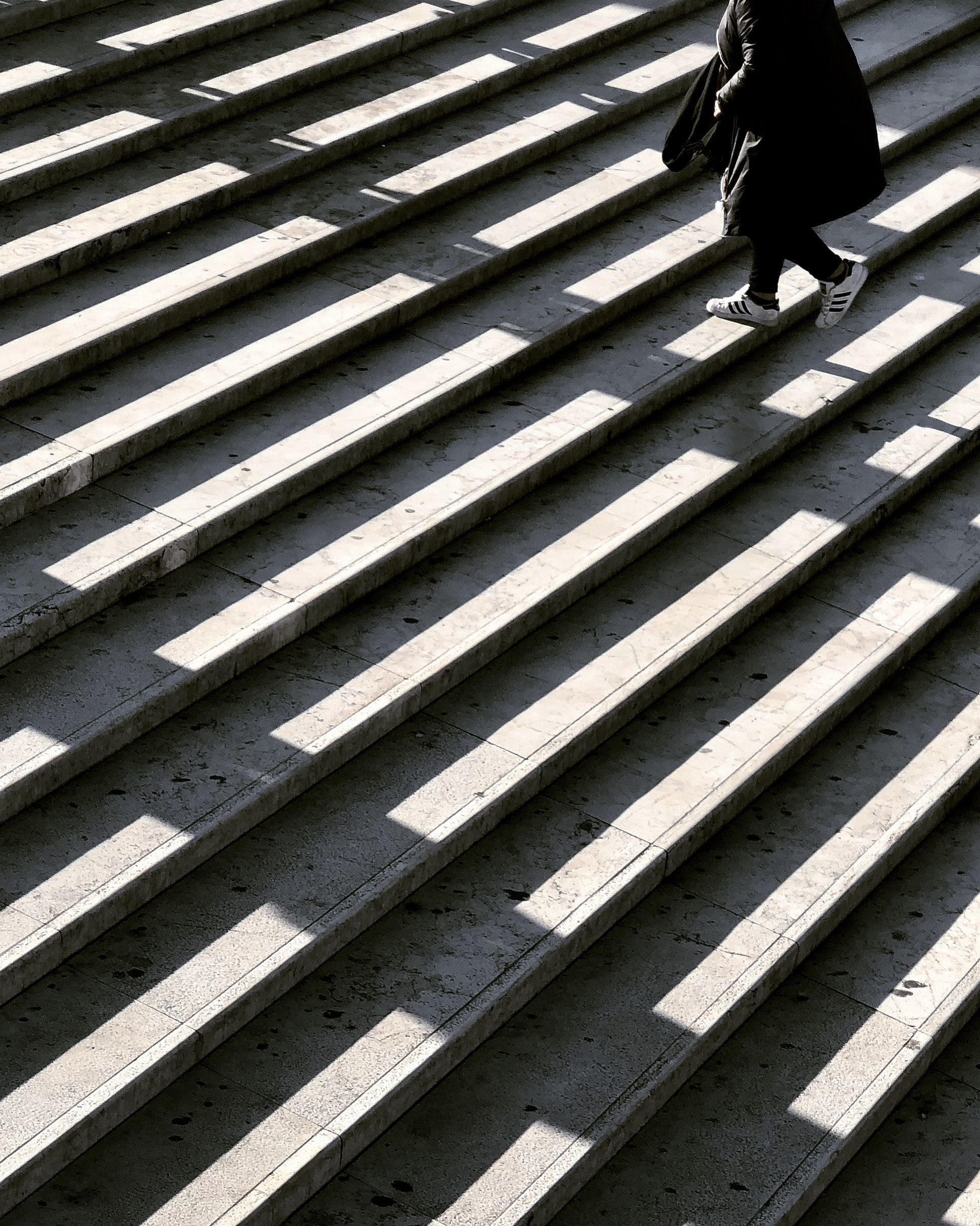 person wearing black jacket walking on stair photography