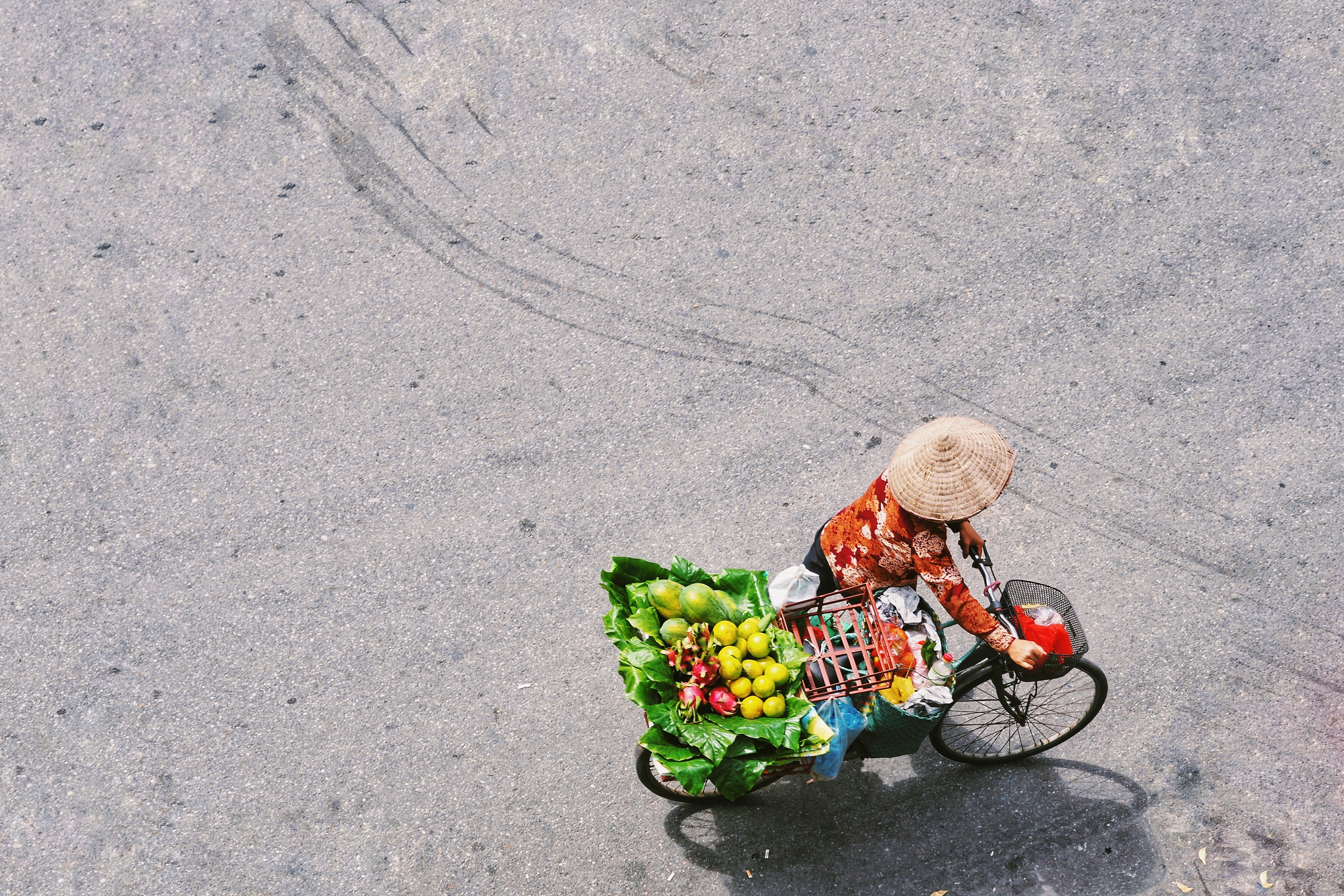person carrying black bike with basket of fruits