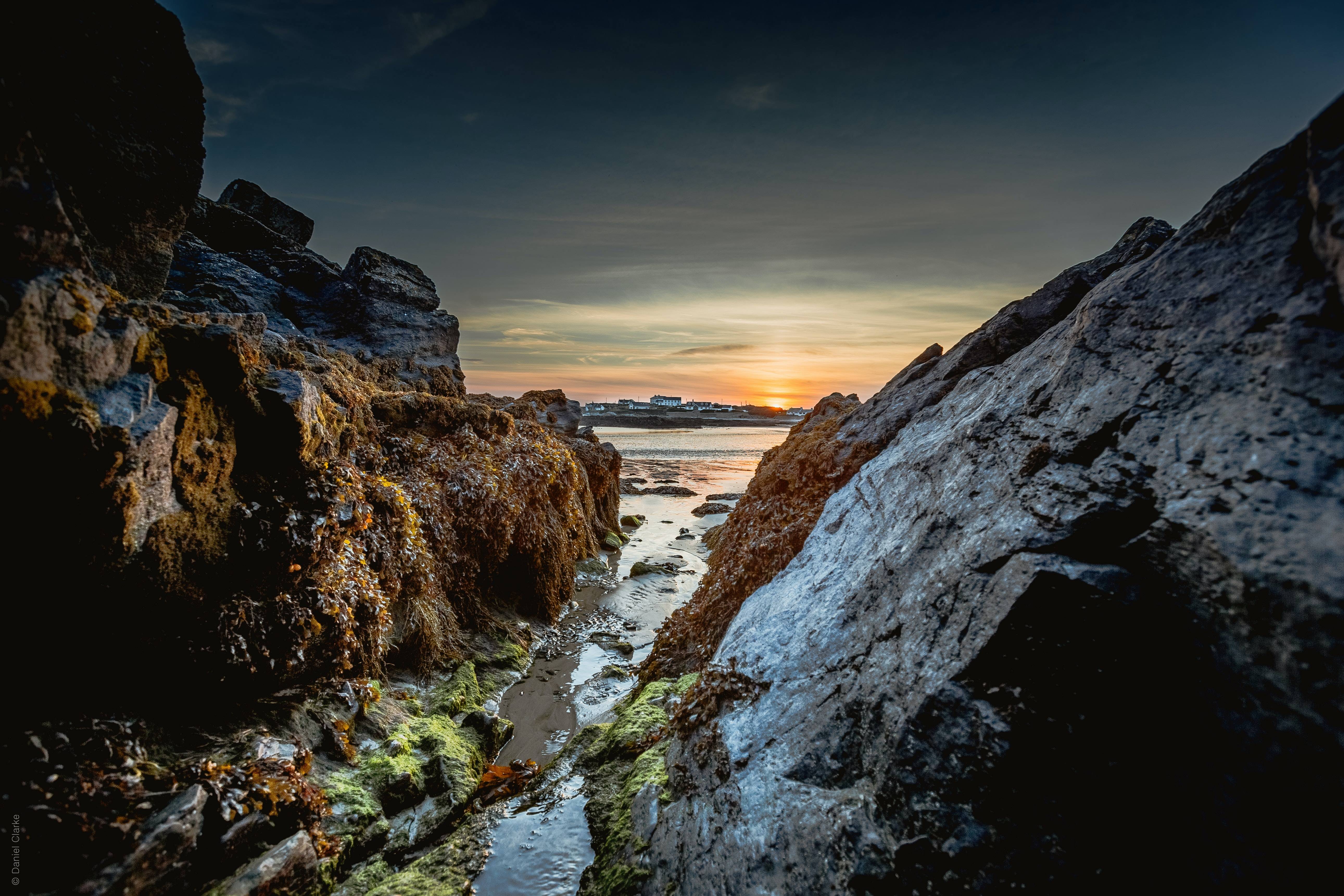 body of water between big rocks under gray and white sky at golden hour