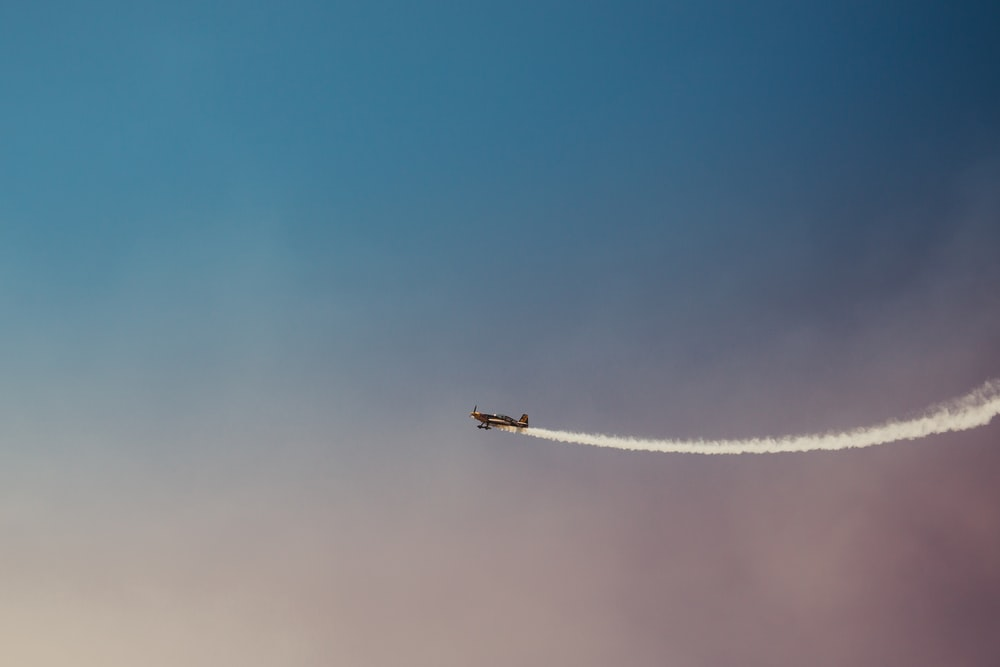 black plane under blue and grey sky