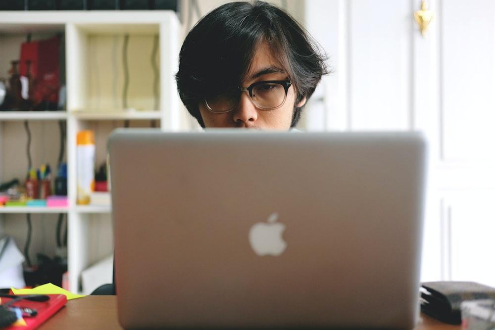 man wearing eyeglasses while using silver Macbook near wooden cubby shelf inside room